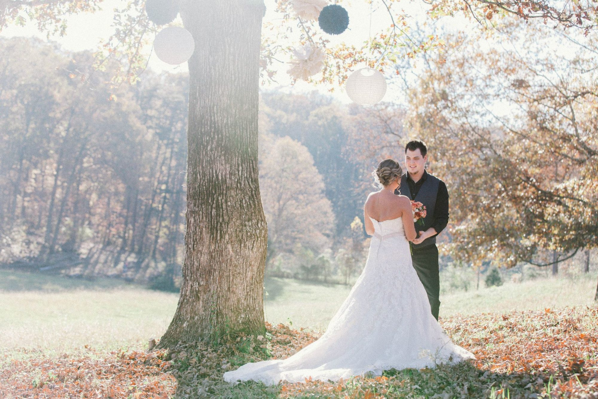 newlyweds under decorated tree