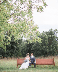 Newlyweds on bench in field